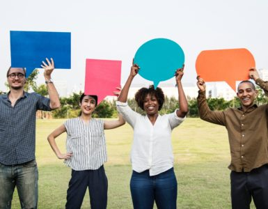 Photo of people holding comment bubbles in a park.